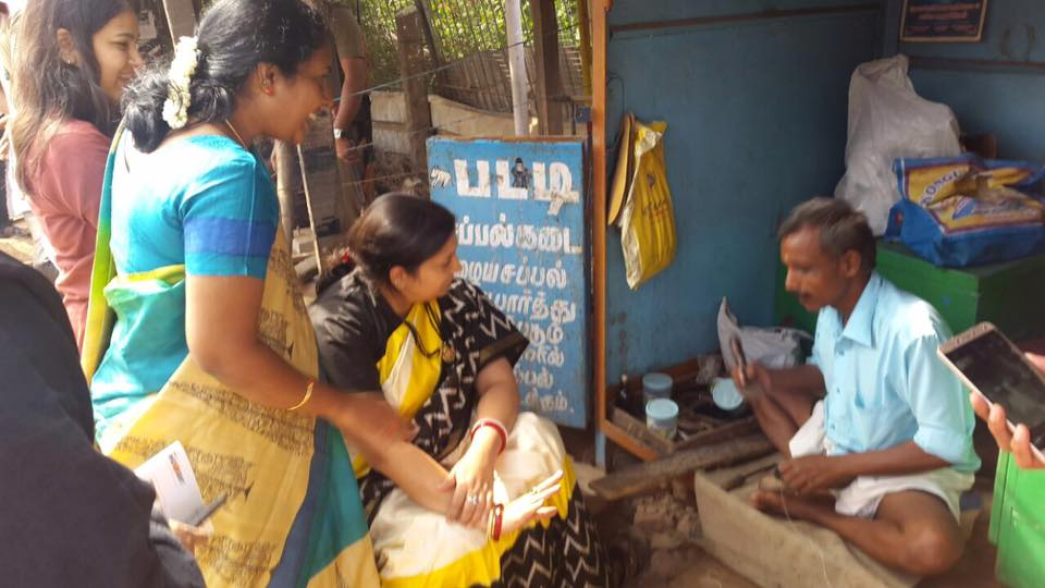 Minister Smriti Irani waiting patiently while the Shopkeeper does the job.